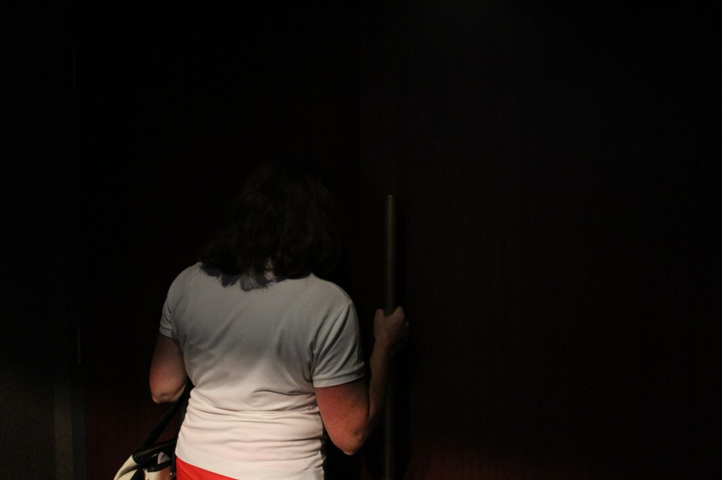 Woman peering through closed door into dark lecture hall