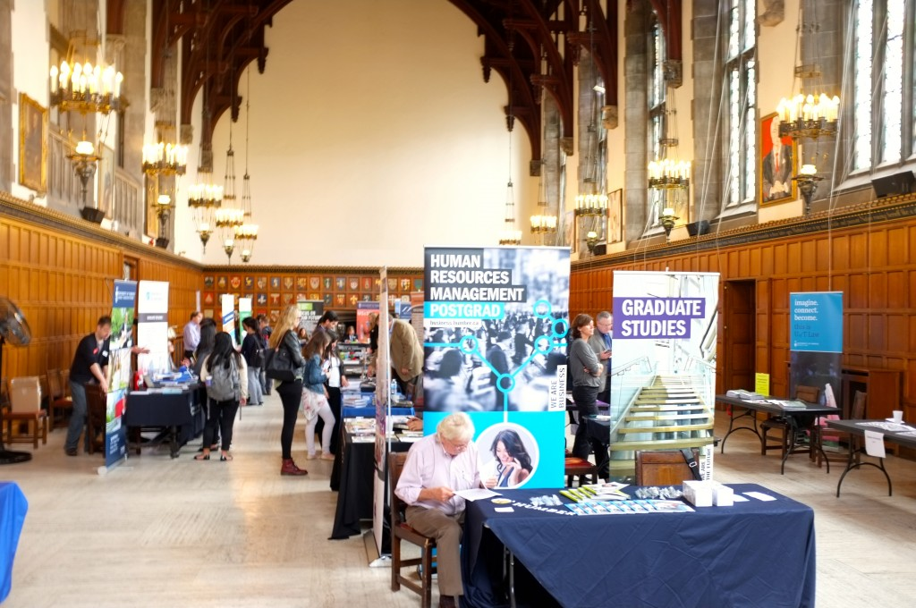 picture of several tables at the grad school fair in the Great Hall in Hart House