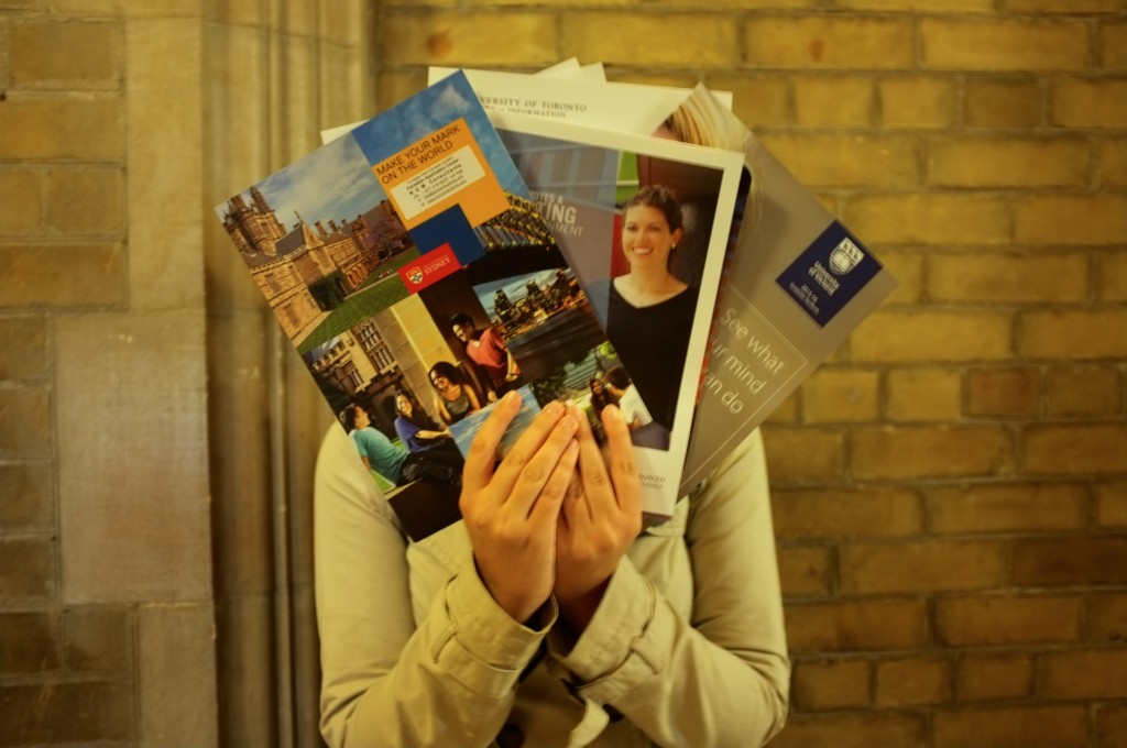 person holding several grad school view books in front of her face