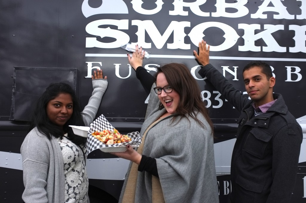 community crew members holding food in front of a urban smoke food truck