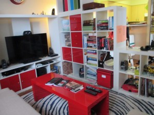 A small living room with tall white bookshelf cubes and TV stand, with a red coffee table and red doors in the white furniture, and with a white with blue ripples in the fabric