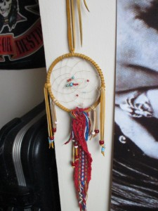 A small dream-catcher with dark red, white, and teal beads and a multicolour cloth from a Métis sash