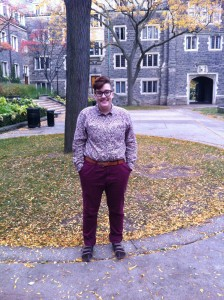 Me at Trinity College's Quad. I am wearing masculine-tailored pant, a baggy floral shirt, with short hair and some running shoes.