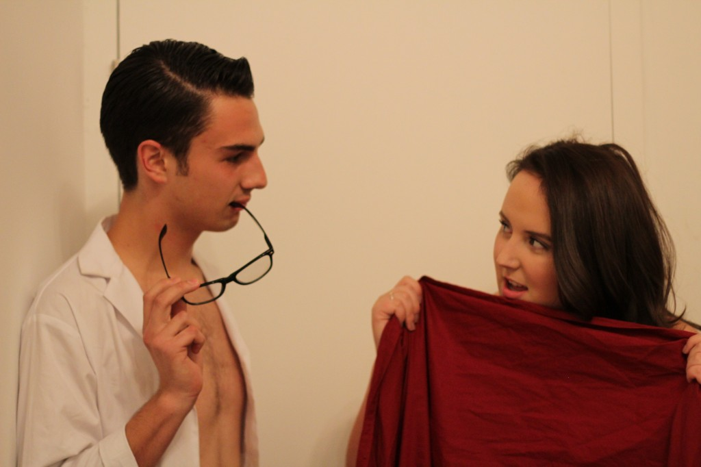 Photo of boy and girl staring at each other seductively, posing heavily for the camera. Man is dressed in a lab coat and white briefs with slicked back hair and nerdy glasses. The girl is hidden behind a large red bed sheet.