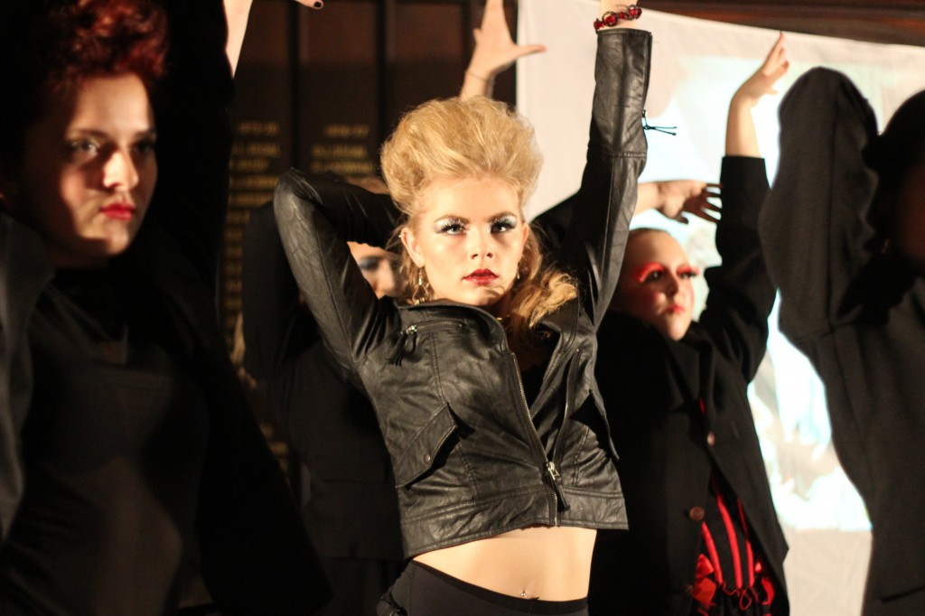 Girl dressed in outlandish costume of leather and fishnets with largely teased hair and over-the-top makeup, throwing her hands in the air dancing.