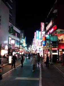 A neon-lit street in Tokyo at night. People can be seen walking along the street.