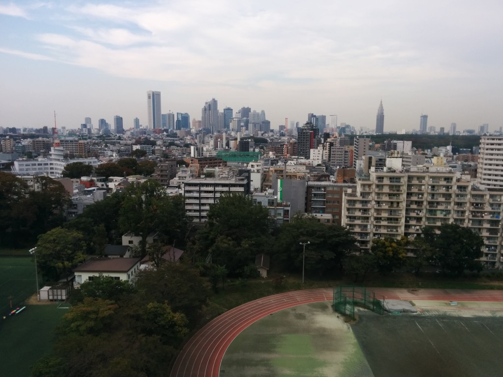 A view of the Shinjuku skyline as seen from the University of Tokyo's Komaba Campus. A running track can be seen in the immediate foreground. Clusters of buildings can be seen beyond the field. A tall skyline (Shinjuku) can be seen in the distance.