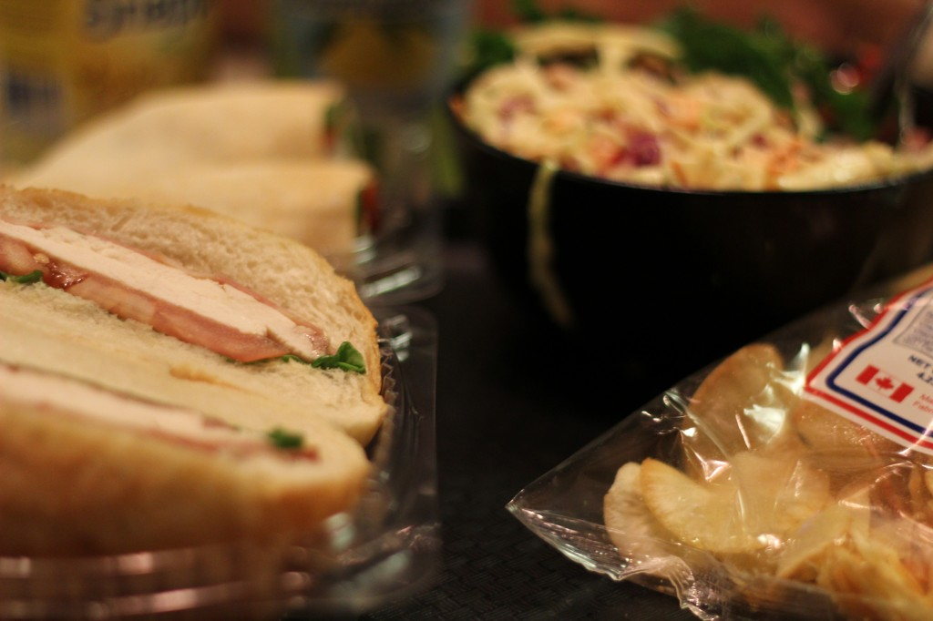 Picture of sandwich, bowl of salad, and bag of chips