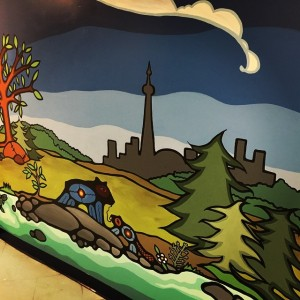A wall mural of a river, forest, and Toronto skyline, with a bear and it's cub, in Indigenous woodland style