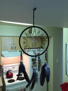 A large dream-catcher with three bundles of feathers, hanging above the bar in my kitchen