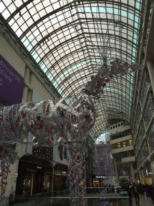 A giant metal reindeer standing in a hall in Eaton Centre, with the big skylight as the backdrop