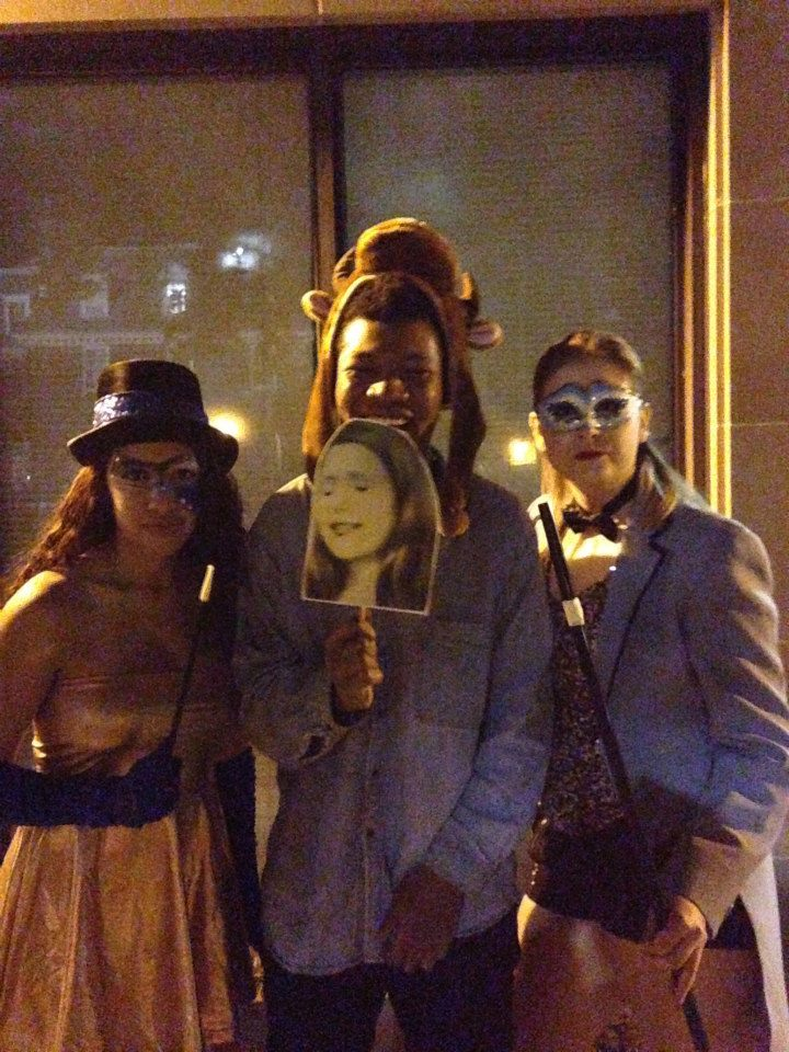 Me posing for a picture with my friends on Halloween. I have a Dollarama cow hat on as my costume; I literally have a denim button up, and black skinny jeans on. I am in the middle with of the picture, and I am holding a picture of my friend's crying face. I am making my squinty laughing face!