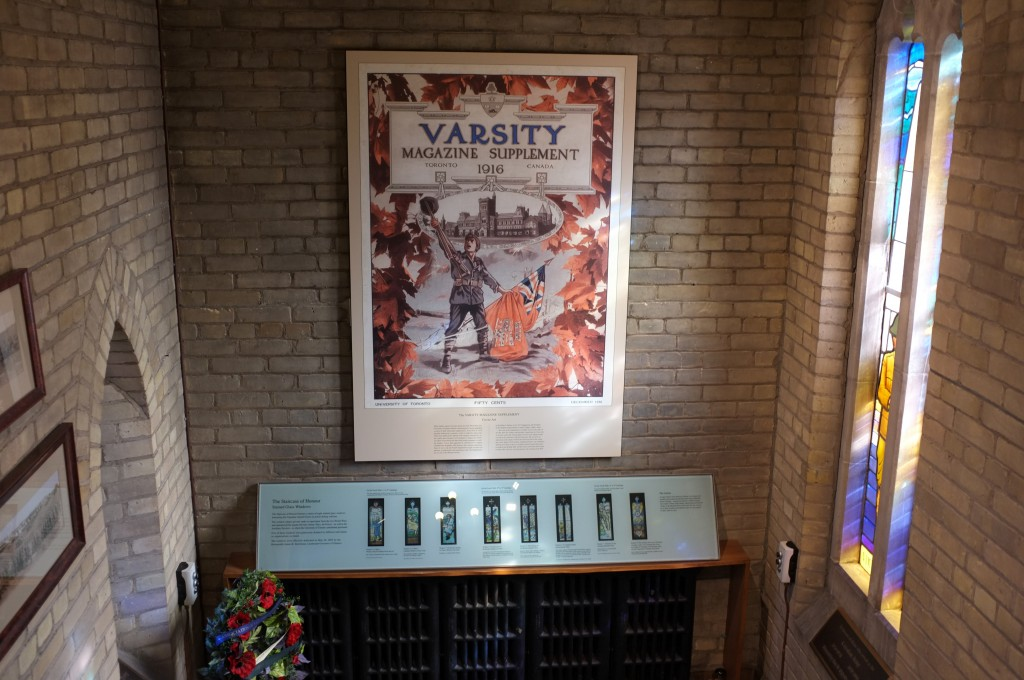 """image showing a view from the top of some stairs of a poster that says """"Varsity Magazine Supplement"""" showing a soldier standing in front of University College holding a gun in the air and a flag in his other hand."""