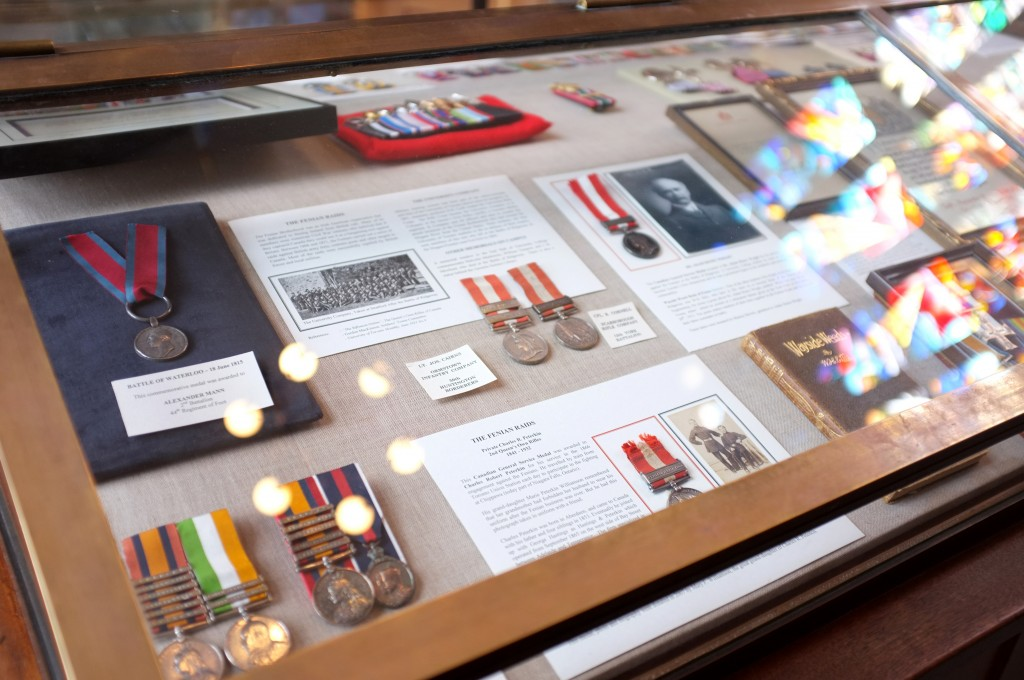 image of a case filled with war medals and pictures with text lables. the coloured light filtering through a stained glass window is reflected in the glass.