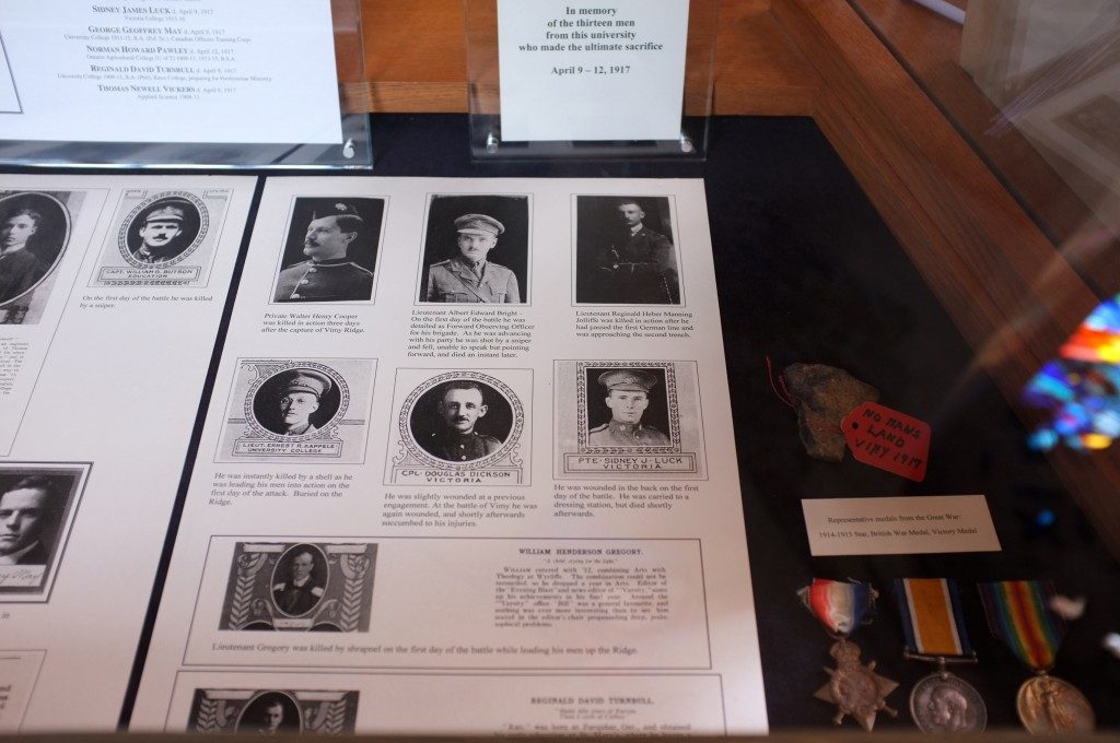 """a case displaying the pictures of university men who died at vimy ridge, also in the case are medals and a rock with a label """"no mans land, vimy 1917."""""""