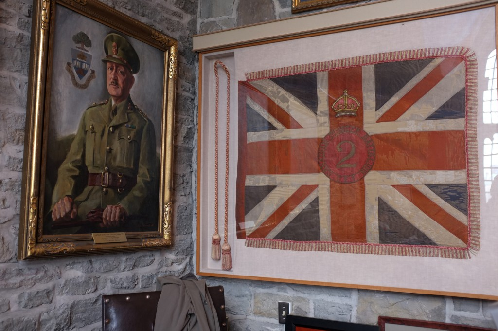 """a painting of a middle aged man in a green army uniform beside a union jack  flag inside a frame. the flag is dirty and rumpled and says """"canadian pioneer batallion 2"""" in the middle of t with the words in a circle around the 2."""