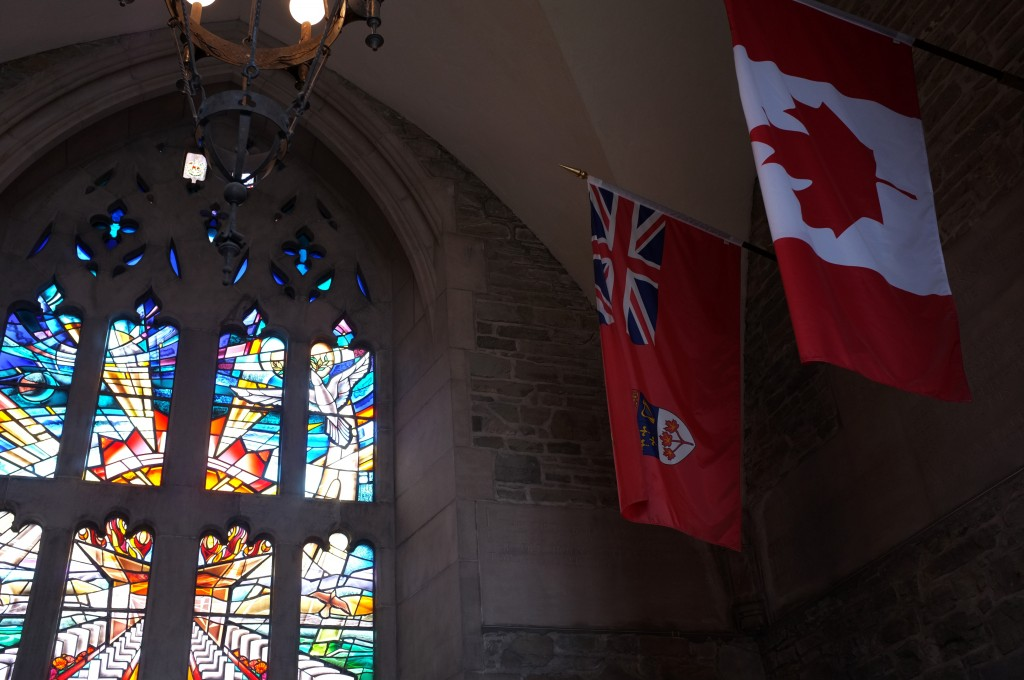 the same stained glass as before shown with an ontario flag and a canada flag hanging from the ceiling beside it
