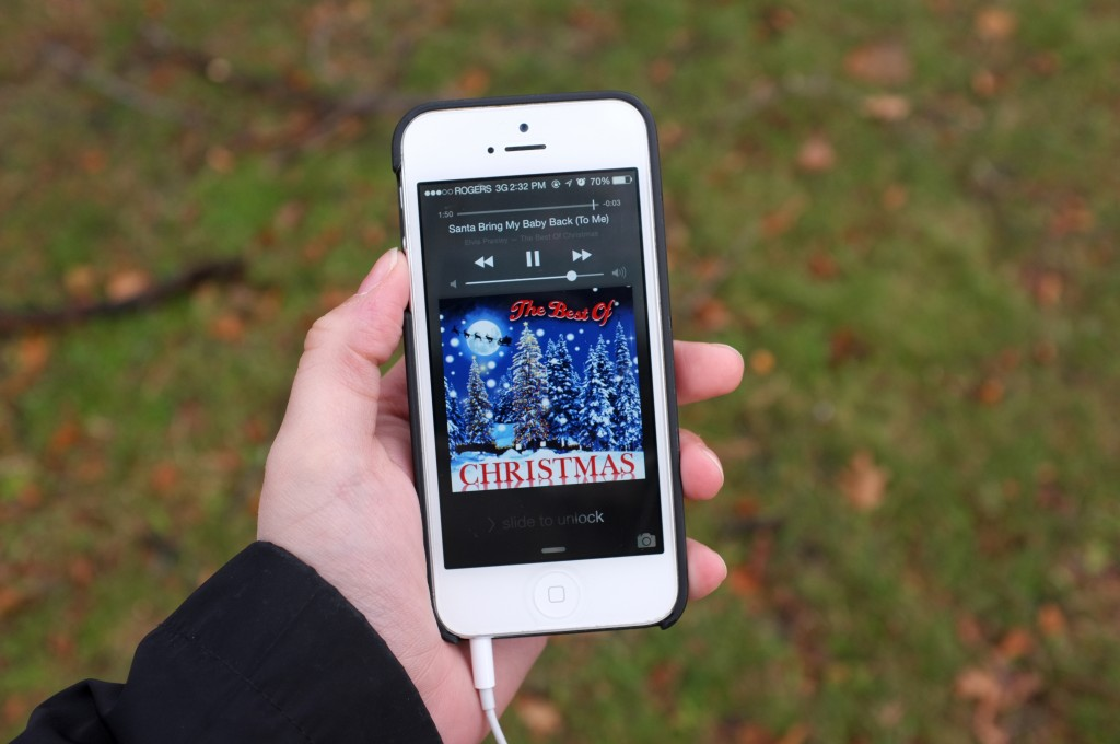 "an Iphone 5 held up in front of grass with an image of a christmas album on it. The song playing is elvis ""santa bring my baby back to me"""