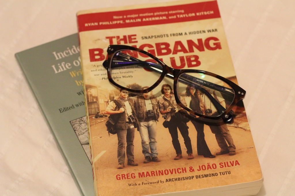 "Picture of book that reads ""The Bang Bang club by Greg Marinovich"" laid out on a bed spread with a pair of reading glasses on top."