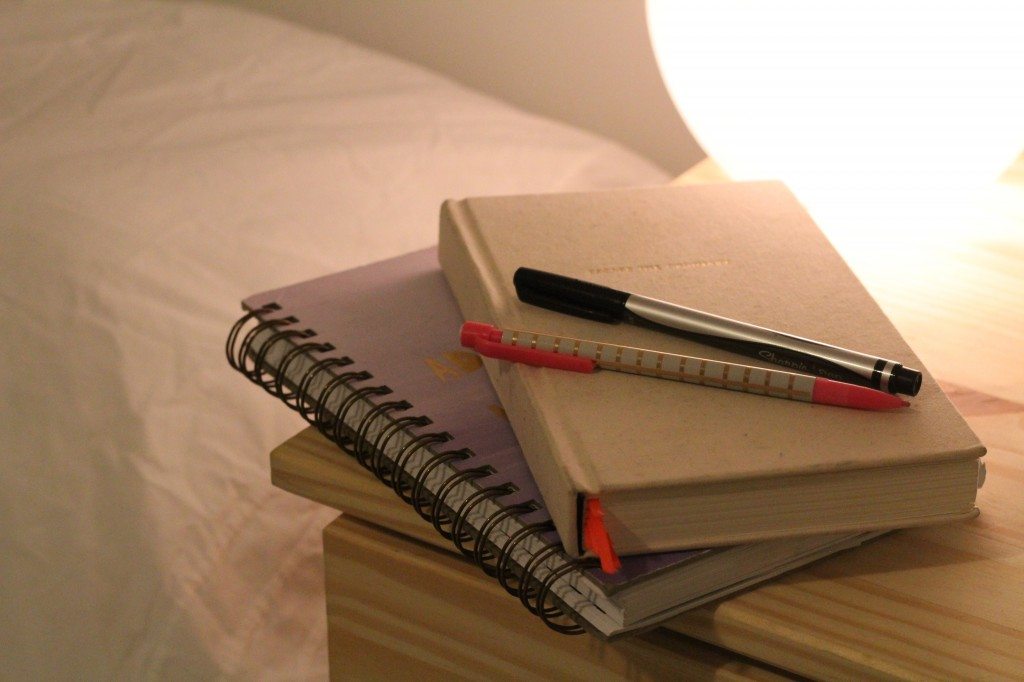 Picture of two paperback journals stacked on top of each other. They're sitting on a wooden dresser next to a white bed with a bedside lamp shining of them.