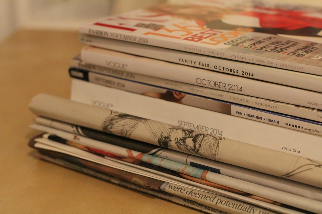 A selection of magazines stacked on top of one another. Titles include various publications such as vanity fair, vogue, and fashion magazine.