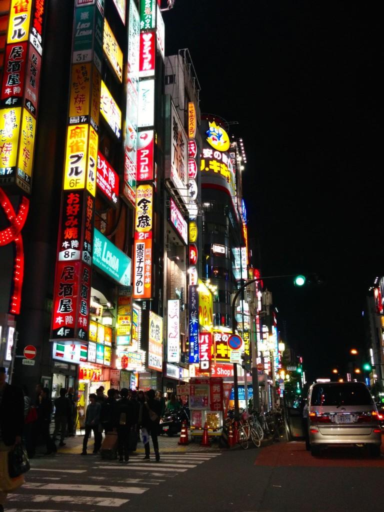 This image shows a neon-lit urban street. It was taken outside Shinjuku Station.