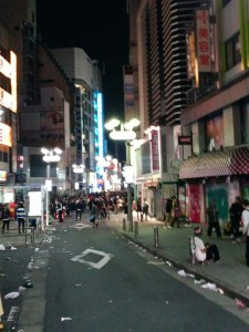 A street in Shibuya at night hoards of people can be seen in the distance. The street is covered in litter.