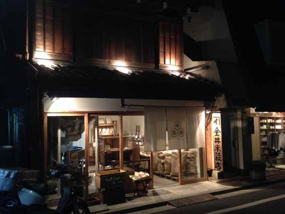 This image shows a building made of wood on an urban street at night time. It is a rice shop. Bags of rice can be seen inside.