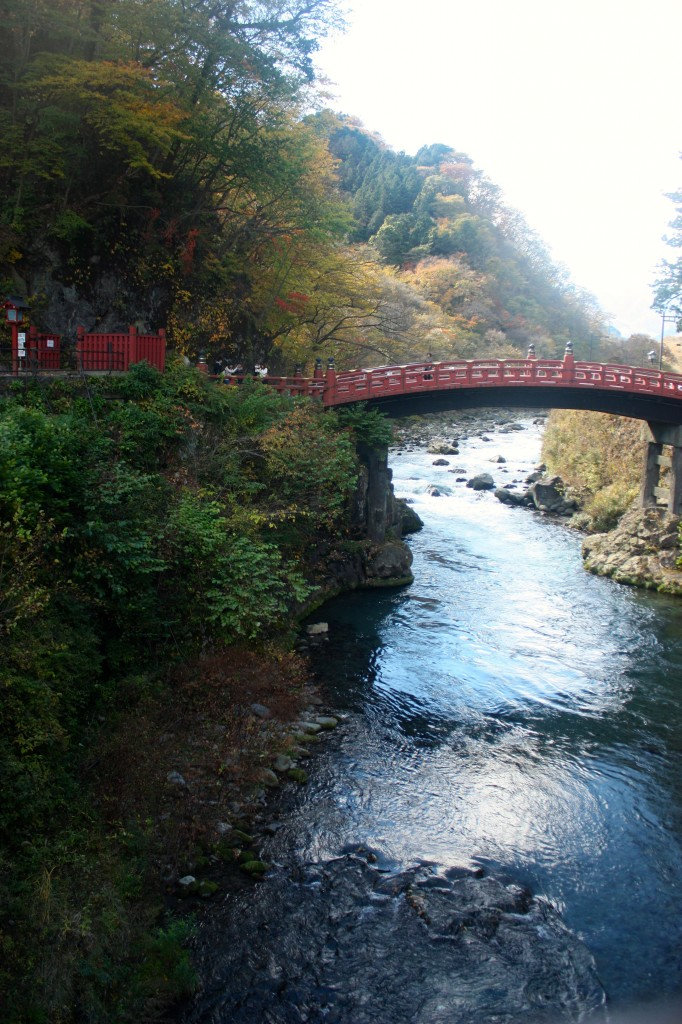 This image shows a red Japanese bridge crossing a river. A forested mountain can be seen in the background.