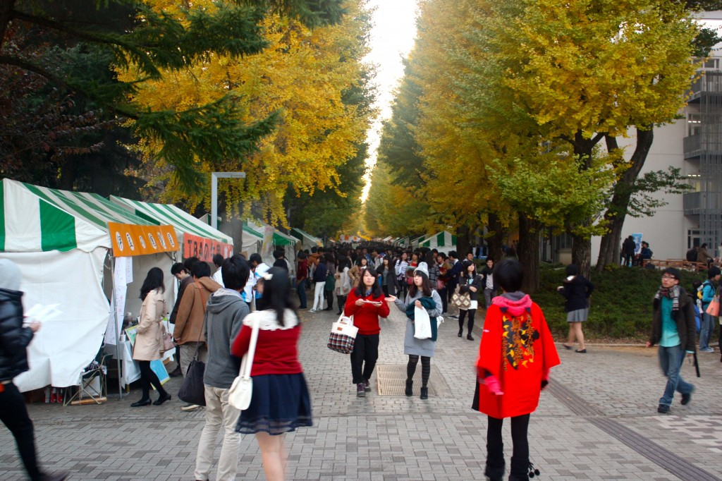 This image shows a corridor at the University of Tokyo, Komaba Campus. It is lined with food vendors. Crowds of people are walking along it.