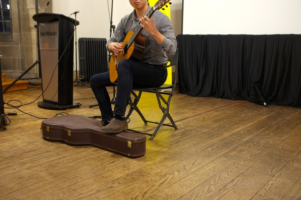 a man sits on a chair playing guitar. His head is out of the frame. A guitar case is on the floor in front of him.