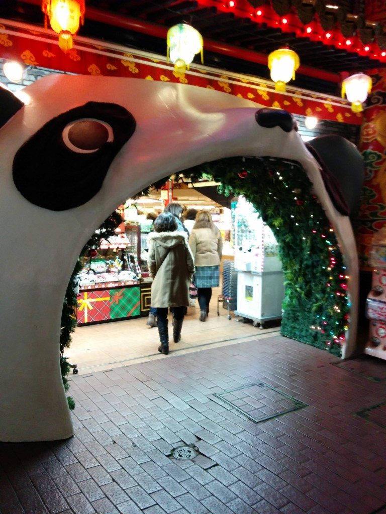 This image show a doorframe shaped like a panda opening its mouth. It is located in Chinatown, Yokohama.