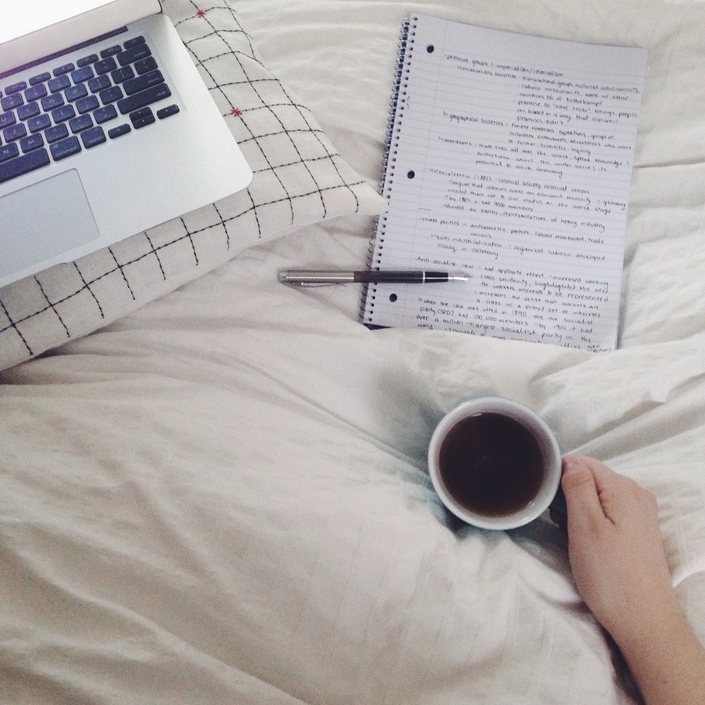 a computer, notebook, and cup of coffee all placed on a fluffy white duvet in a studying setting