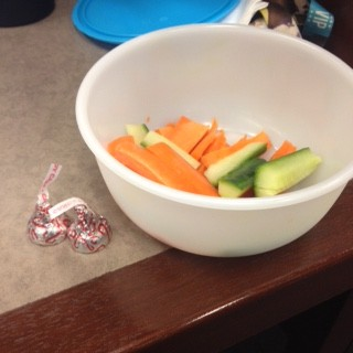 Picture of tupperware with veggies sitting next to chocolate on the desk