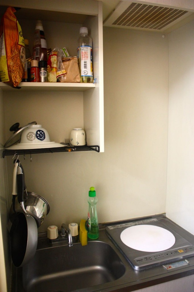 This image shows a kitchenette featuring a burner, a sink, and a pantry.