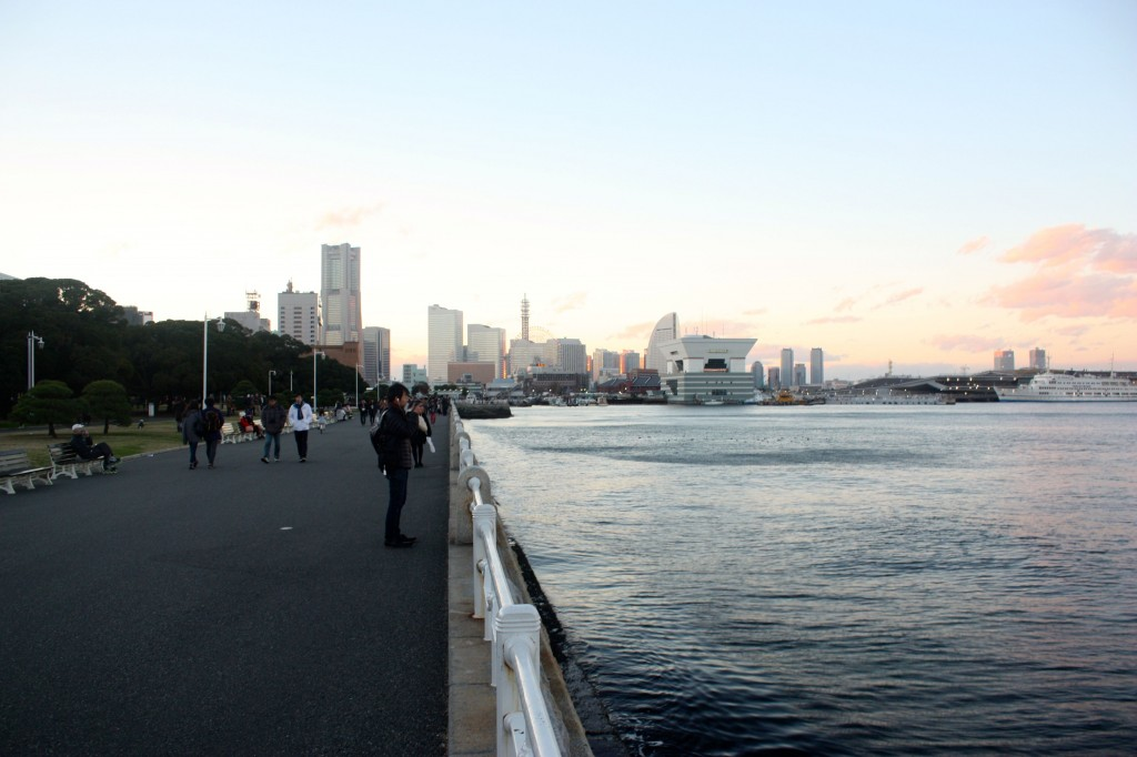 This image shows Yokohama's port and skyline. A paved road runs along the seashore.