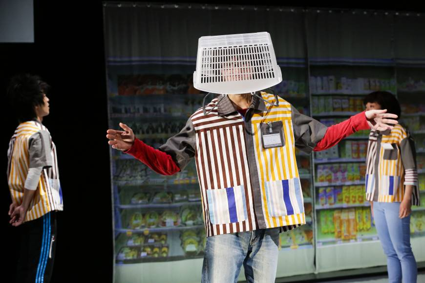 "This image shows a scene from the play ""Super Premium Soft W Vanilla Rich."" Three actors can be seen. Two are facing each other in the background. One is wearing a shopping basket on his head in the foreground."