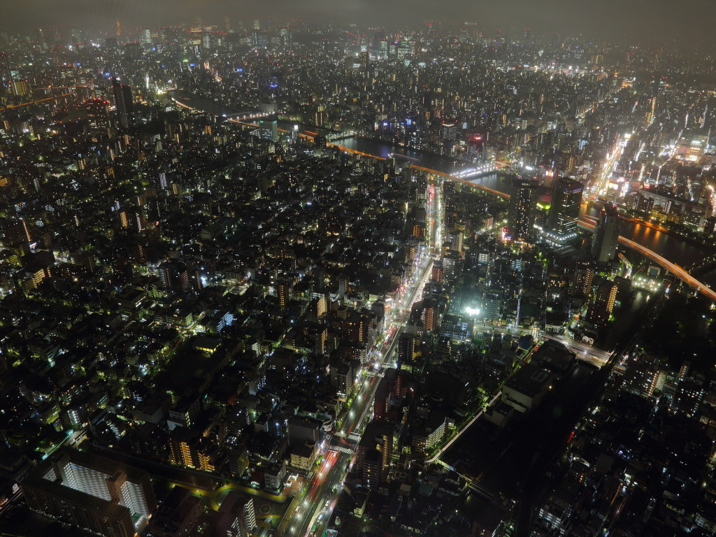 This image shows Tokyo's Roppongi neighbourhood at night from an aerial view. Neon-lit skyscrapers fill the image. A river intersected the clusters of buildings.