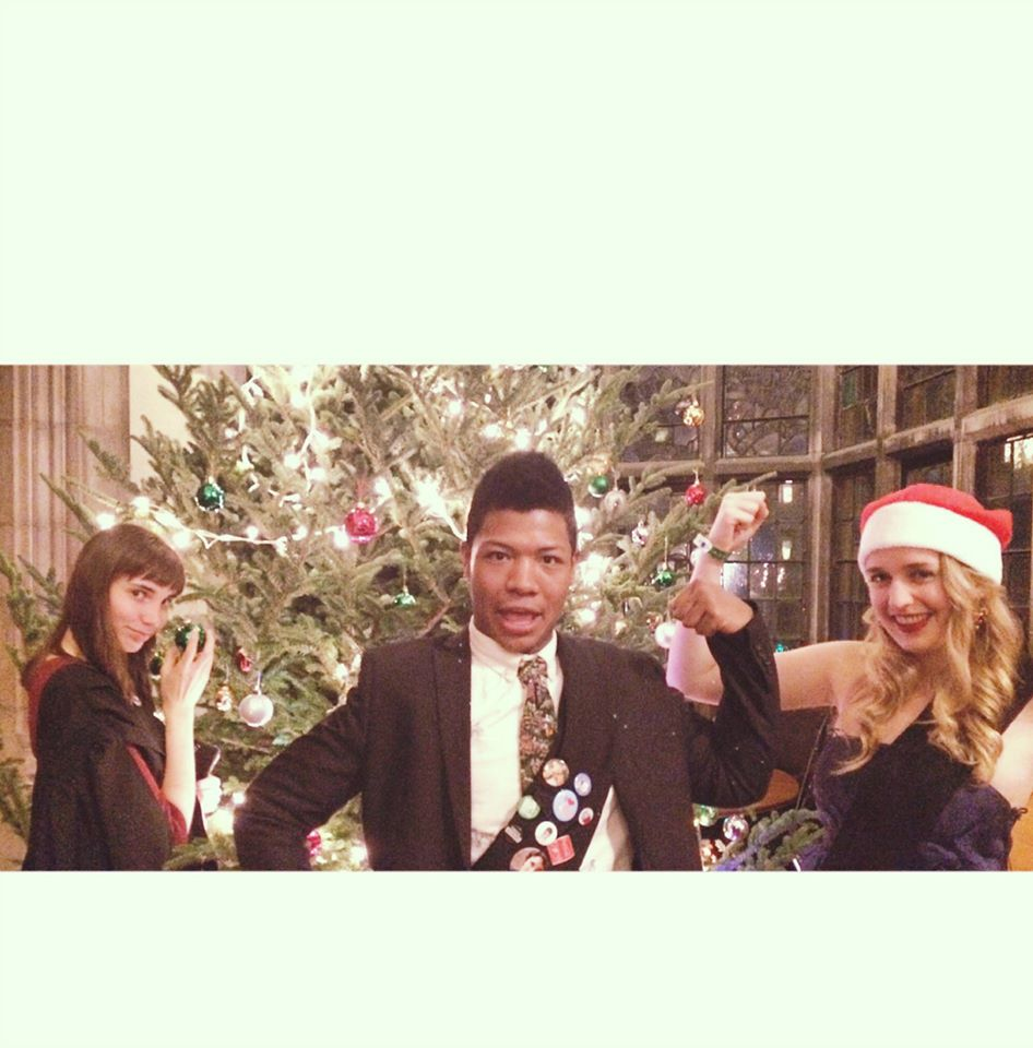 A picture of me and my two friends posing in front of a Christmas tree. We're all dressed formally while making silly Destiny's Child poses.