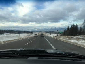 A view from the front passenger seat of a truck, on the highway heading west towards the Rockies, with snow and evergreens all around