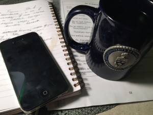 A black iPhone 4, sitting precariously close to a mug of coffee