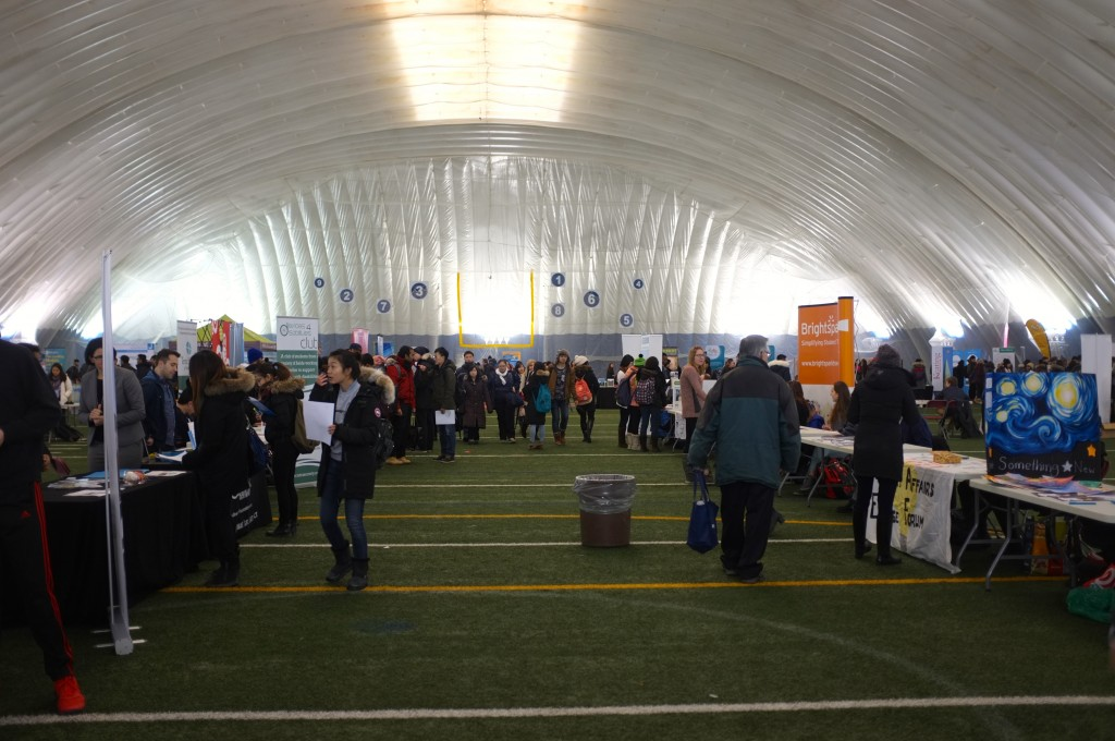 a wide shot of the inside of the varsity dome, there are lots of tables with poster boards and people clustered around them