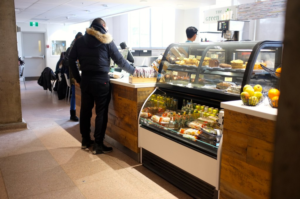 a picture showing a counter with people ordering food. in the foreground is a grab and go section with drinks and snacks that you can grab.
