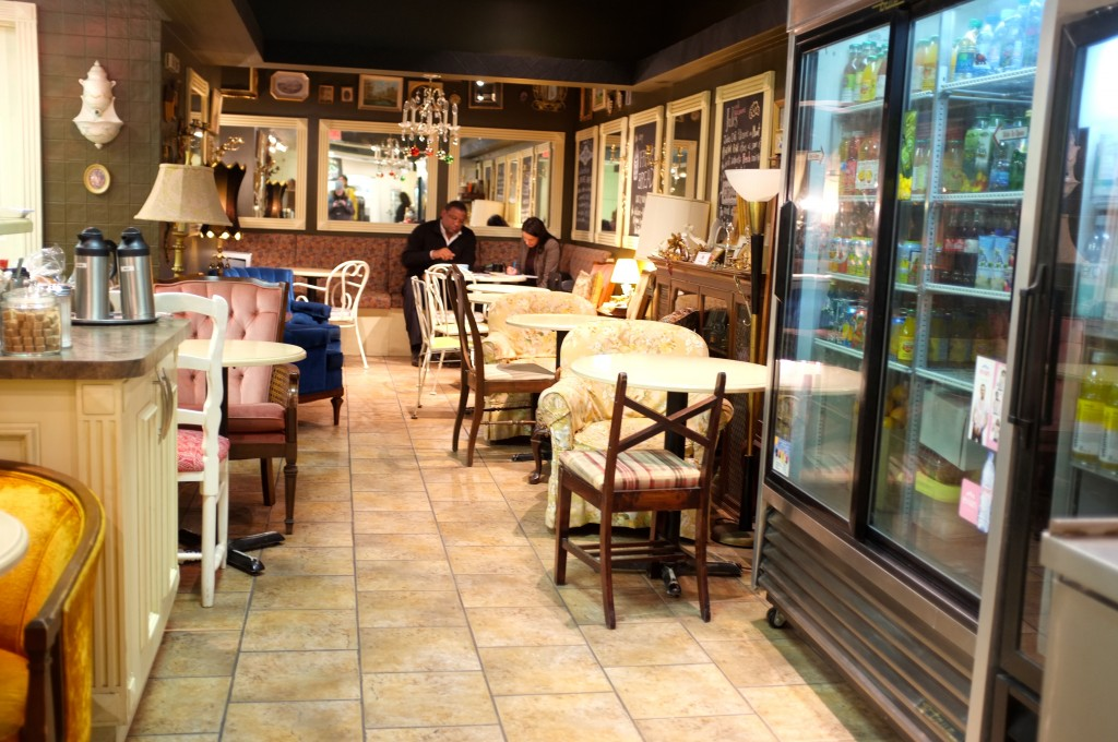 the inside of a small, narrow cafe are shown, against the walls are mismatched tables and plush chairs. on the walls are mirrors and pictures.