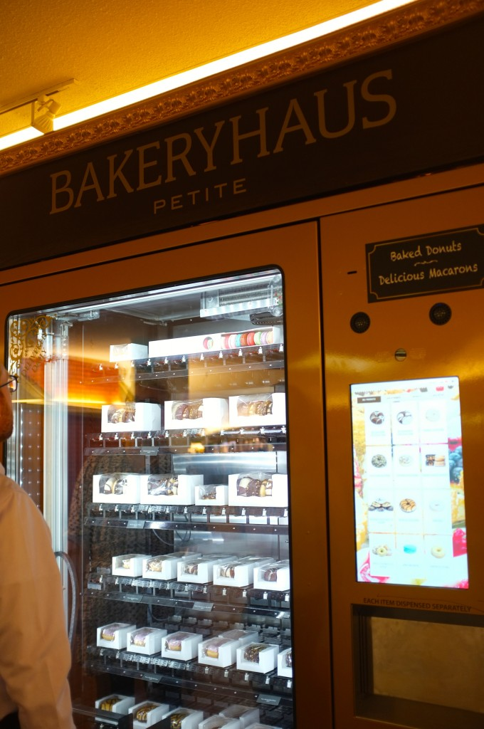 "a vending machine with the word ""Bakeryhaus"" at the top. The inside is lit up and you can see donuts and macarons inside. To the left of the glass is a touch screen where you imput what you want."