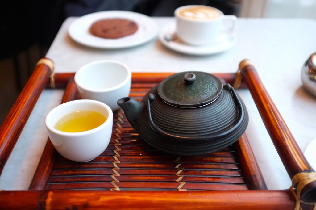 a small black teapot and two small white teacups (one filled) sit on a brown wooden tray.