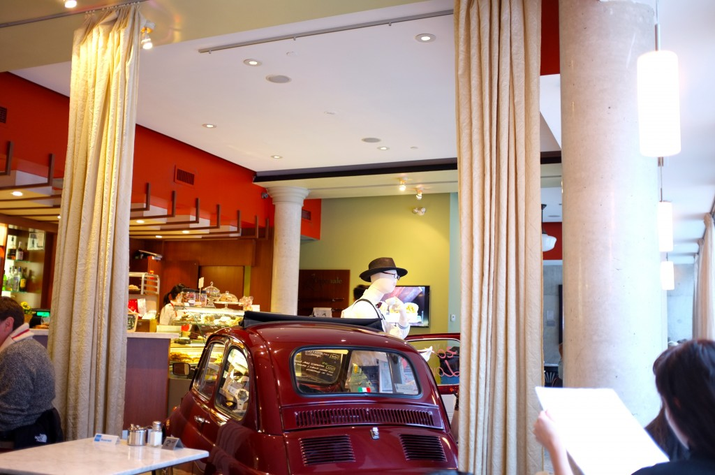 the inside of a cafe with a small red car parked among the tables. In the back you can see the counter and the food fridge.
