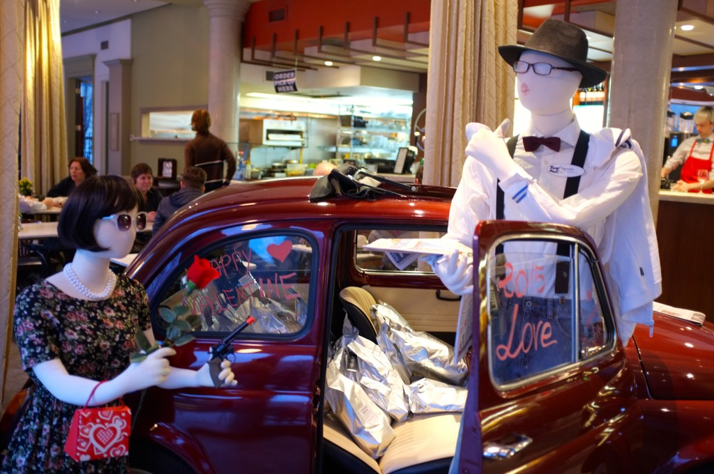 a small red car inside a cafe. the door of the car is open and inside are bags of coffee. In front of the open door are two white mannequins, one of which is proposing to the other with a red rose. the other is standing and wearing a boytie and hat.