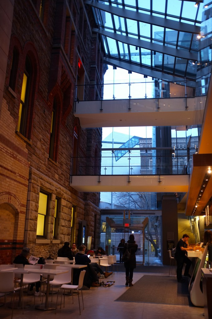 a hallway with white tables and chairs on the left side against an old wall and a cafe counter on the right side against a new wall. in the background is a glass entranceway. the ceiling is made of slanted glass and brides between the outside of two buildings forming a hallway.