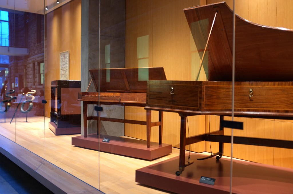 3 old pianos inside a glass case